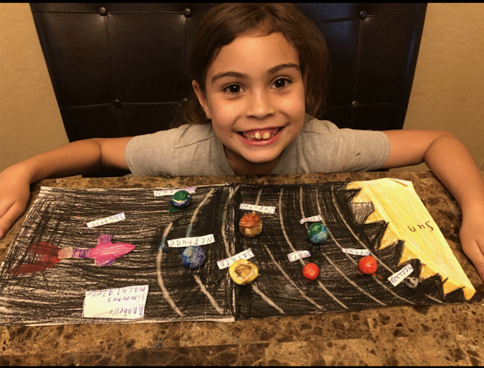Third Grader Anabella Simmons showcases her solar system model.