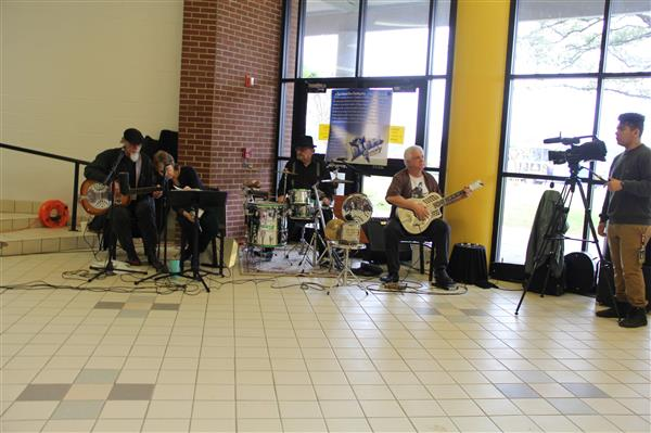 Neesie and the Tin Can Trio plays for students in the high school.