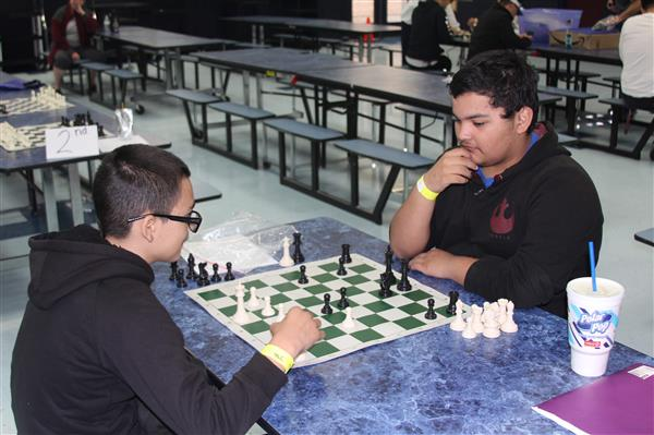 Students engage in tense chess battle.