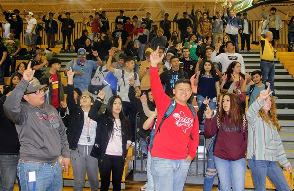 Students show spirit during the school song.