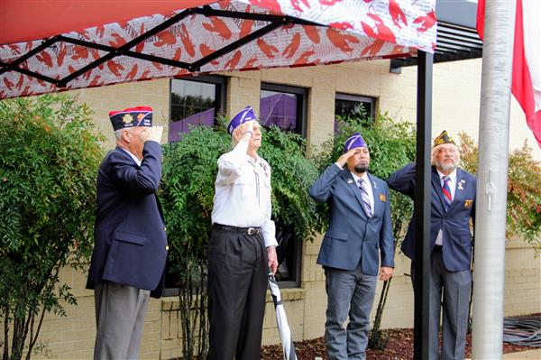 Purple Heart veterans salute the flag.