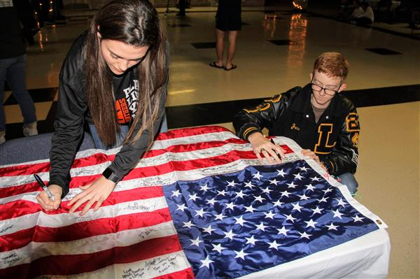 Well wishers sign the flag as a memento of Ronan's time in Lytle.